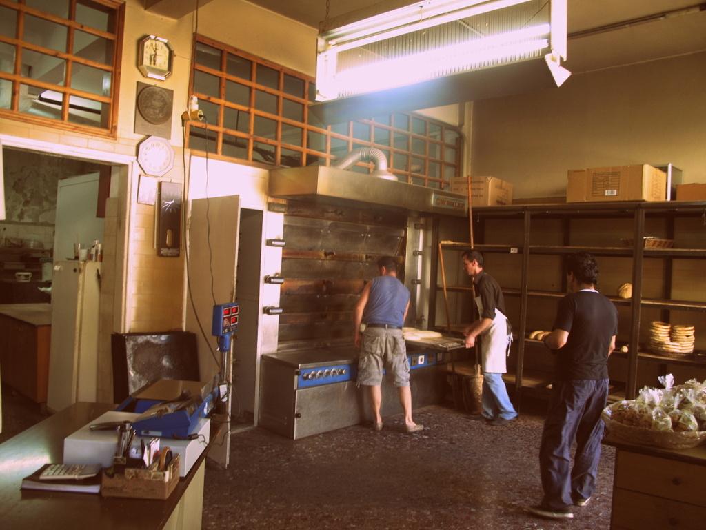 Der Ladenraum ist zugleich auch die eigentliche Bäckerei. Die Brote werden auf lange Bleche gelegt, die wie in einem (so meine Assoziation) Leichenschauhaus aus ihren Fächern gefahren kommen, um dann …