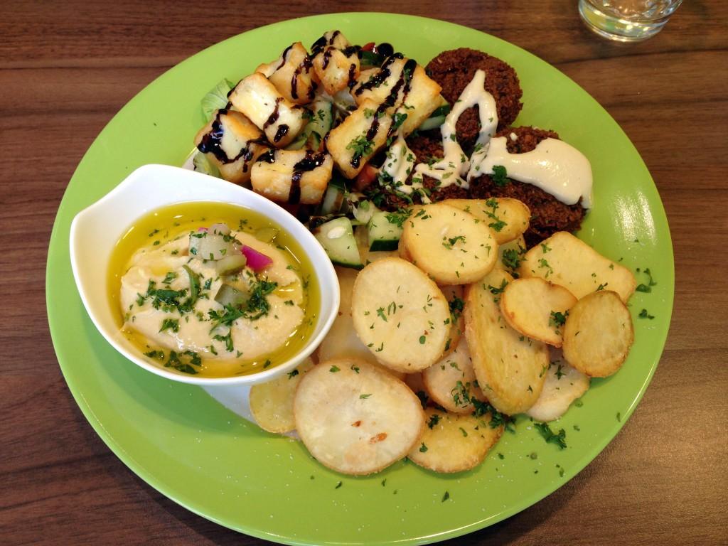 Halloumi-Falafel-Teller mit Bratkartoffeln, Hummus und Salat.